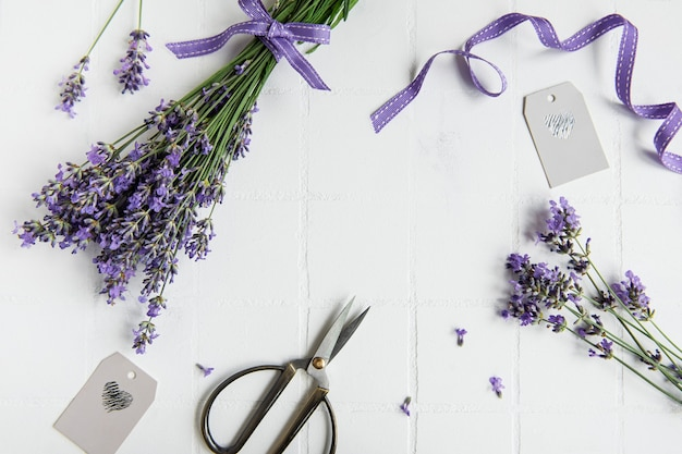 Lavender flowers, scissors and ribbon  on a white tile background