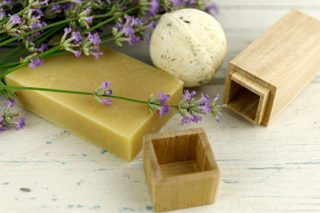 Lavender flowers on shaby white wooden table with bokeh and soap.
