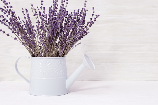 Lavender flowers in watering can, old wooden background