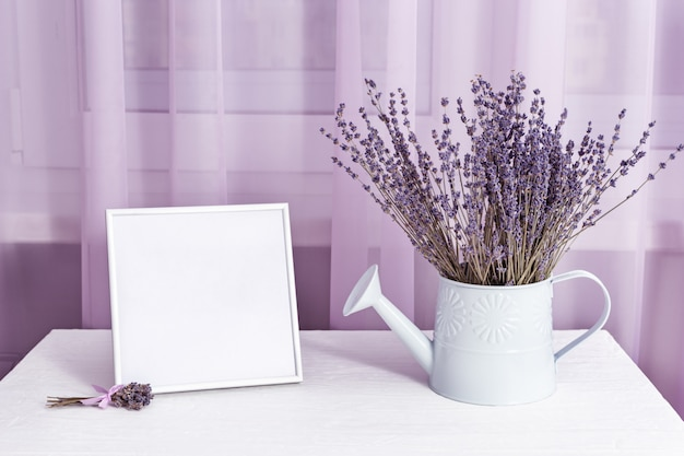 Lavender flowers in watering can and photo frame