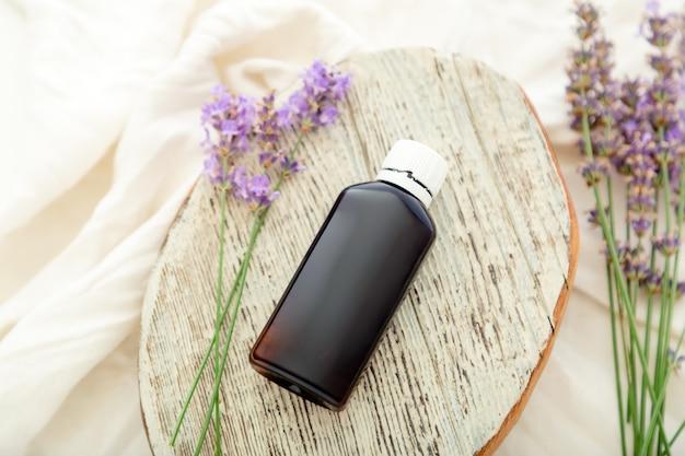 白い木製の素朴なボードとファブリックにラベンダーエッセンシャルオイルボトルとラベンダーの花。アロマテラピートリートメント、天然オーガニックスパ化粧品、ホメオパシー薬剤師ラベンダーハーブ。