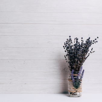 Lavender in the glass on desk against wooden background