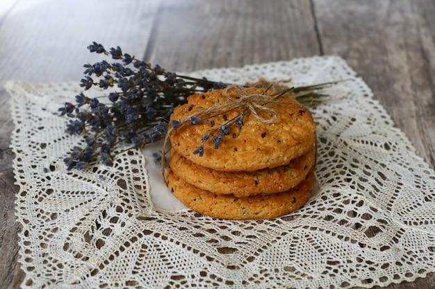 木製の背景に、レースのナプキンにラベンダーの手作りクッキー