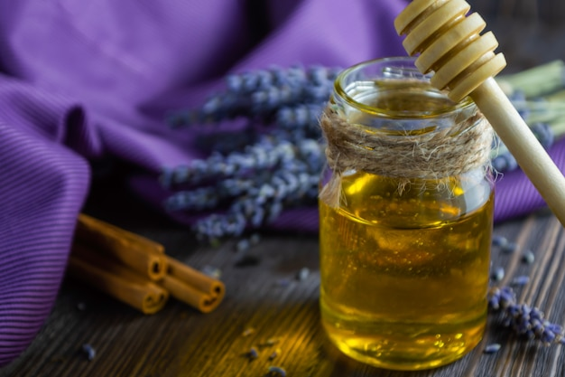 Lavender and herbal honey in glass jar on dark wooden table.