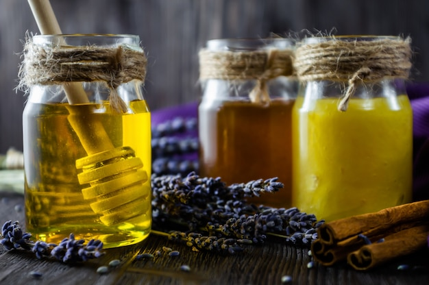Lavender and herbal honey in glass jars on dark wooden table.