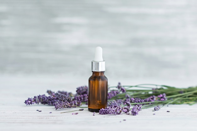 Lavender herbal oil and lavender flowers on grey wooden background.