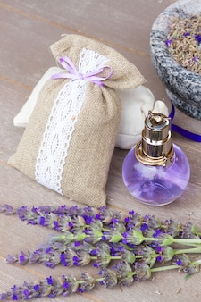 Lavender herbal water in a  bottle with fresh and dry flowers on wooden table