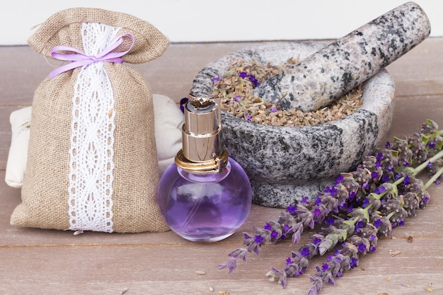 Lavender herbal water in a glass bottle with fresh and dry flowers on  table