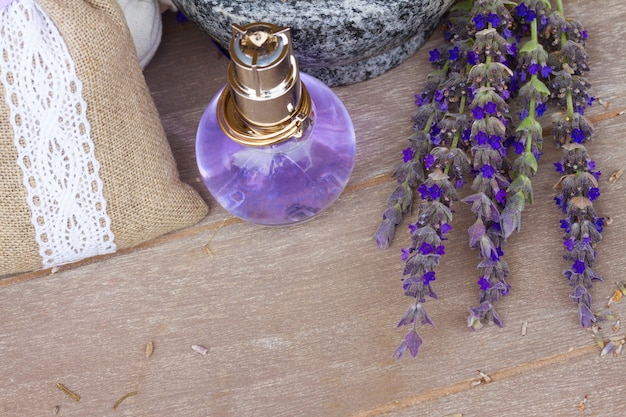 Lavender herbal water in a glass bottle with fresh and dry flowers on wooden table