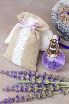 나무 테이블에 신선하고 마른 꽃과 병에 라벤더 허브 물