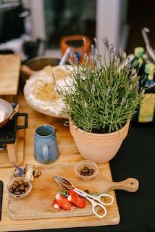 Лаванда в цветочном горшке на кухонном столе с синей кружкой и деревянной разделочной доской