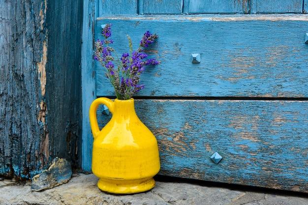 파란색 초라한 문 배경에 노란색 kouvinum에 라벤더