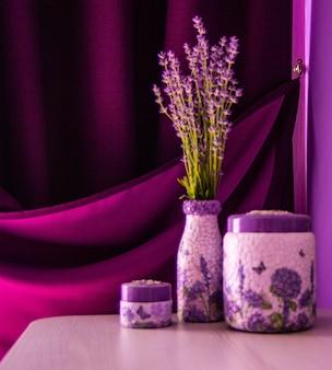 Лаванда в вазе на столе. фиолетовый занавес и фиолетовый фон стены.
