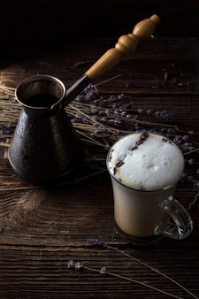 Lavender latte or raf coffee with lavender twigs on background. trendy dark and moody style