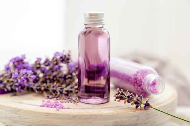ラベンダー液。白い木の板の新鮮なラベンダーの花のボトルのバス化粧品