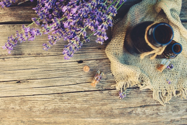 Lavender oil in different bottles on wooden background. toned image. top view.