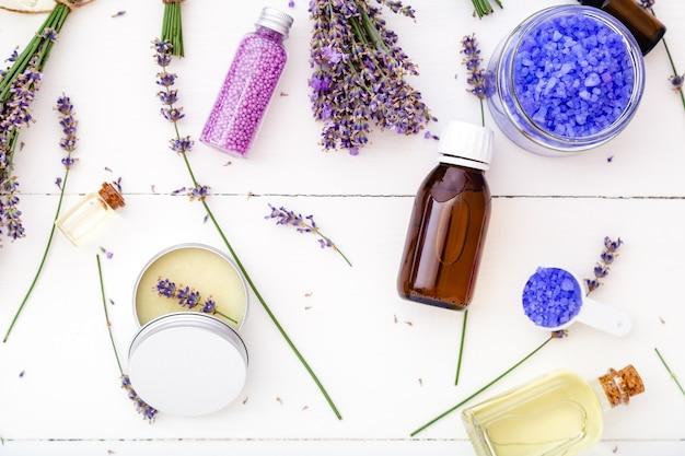 라벤더 약국 의약품 목욕 제품 및 라벤더 꽃. 비누 바다 소금 에센셜 오일, 바디 버터, 마사지 오일, 액체. 평평한 흰색 나무 배경. 스킨케어 스파 뷰티 코스메틱.