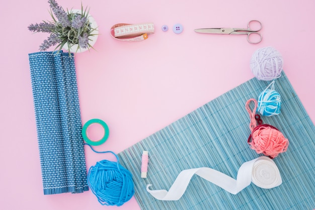 Lavender potted plant with measuring tape; button; scissor; placemat; wool; spool and ribbon on pink background