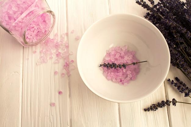白い木の表面にラベンダーの塩と花。上面図。