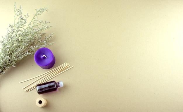 Масло с ароматом лаванды в бутылке с фиолетовыми свечами, деревянными палочками и сухими цветами, лежащими на столе