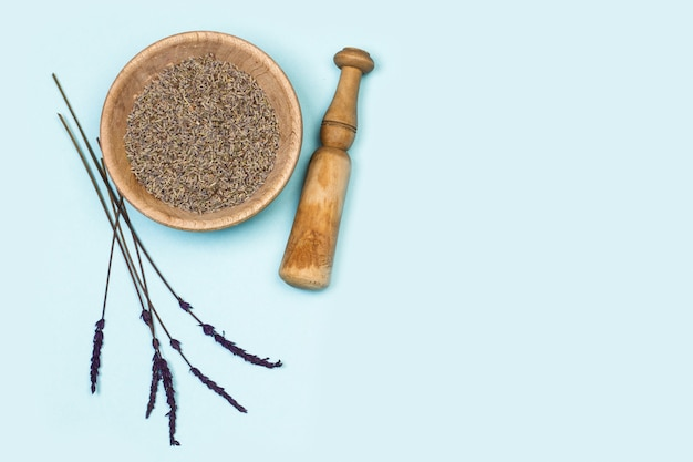 Lavender seeds in a wooden bowl on a light blue background