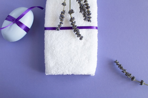 Мыло лаванды и белое полотенце на фиолетовом фоне. вид сверху.