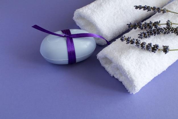 紫の表面にラベンダー石鹸と白いタオル