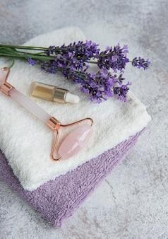ラベンダースパ。エッセンシャルオイル、フェイスローラー、タオル。ラベンダーの花と天然ハーブ化粧品