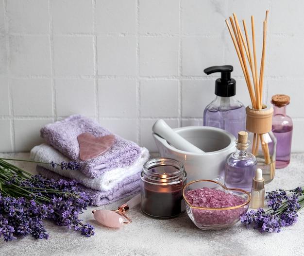 ラベンダースパ。エッセンシャルオイル、海塩、タオル、フェイスローラー。ラベンダーの花と天然ハーブ化粧品
