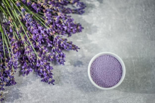 Lavender spa. lavender flowers and bath salt in bowl on light gray.