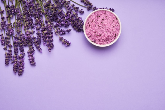 Lavender spa. lavender flowers and bath salt in bowl on purple background. copy space, top view. spa