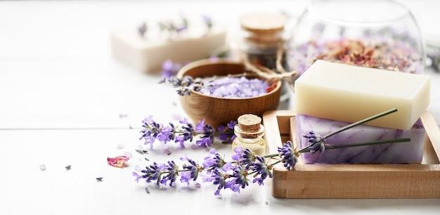 라벤더 스파 제품과 흰색 테이블에 라벤더 꽃. 나무 비누 접시, 에센셜 오일 및 라벤더 목욕 소금에 수제 비누-미용 치료.