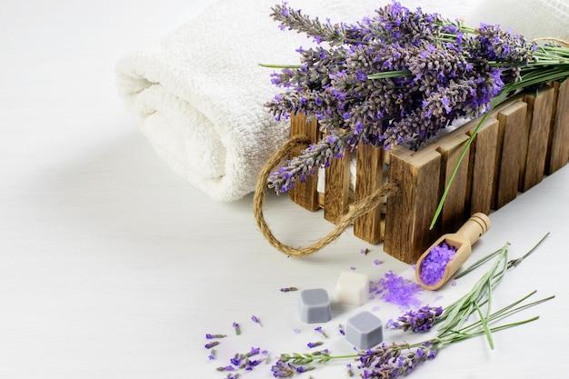 Веточки лаванды, ароматическая соль и мыло, белые полотенца на деревянном столе. деревенский курорт оздоровительный образ жизни, забота о здоровье.