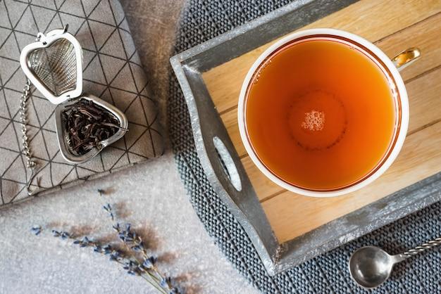 도자기 컵에 있는 라벤더 차와 밝은 회색 대리석 테이블에 있는 라벤더 잔가지.