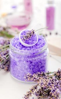 라벤더 꽃과 라벤더 바이올렛 바다 소금. 라벤더 목욕 제품 흰색 나무 바탕에 아로마 테라피 치료입니다. 휴식을 위한 스킨케어 스파 뷰티 목욕 화장품.