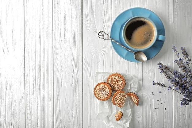 木製の背景にコーヒーとクッキーとラベンダー