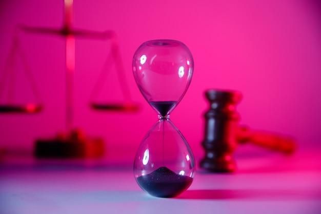Тема закона и справедливости, песочные часы, весы и деревянный молоток судьи в розовом неоновом крупном плане.