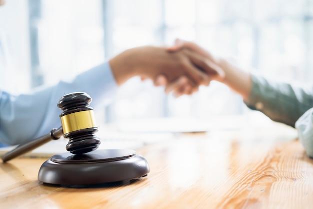法律および法務サービスのコンセプトです。弁護士と弁護士が法律事務所でチーム会議を行っています。弁護士と実業家の握手。