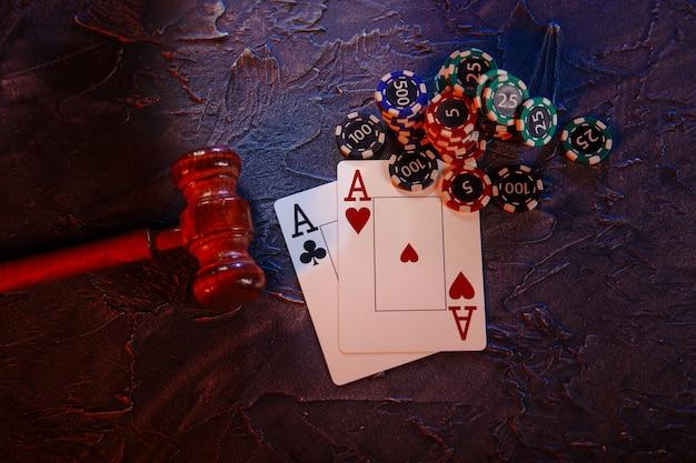 オンラインカジノの概念に関する法律と規則、灰色の背景にエースとプレイチップを備えたジャッジガベル