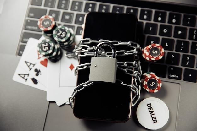 オンラインカジノのコンセプト、南京錠付きスマートフォン、キーボードのポテトチップスに関する法律と規則