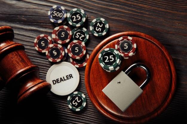 オンラインギャンブルの概念に関する法律と規則、木製の表面に南京錠とエースで小槌を判断する