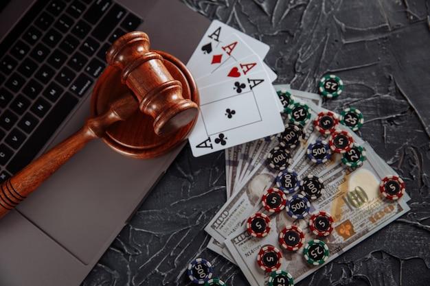 オンラインギャンブルの概念に関する法律と規則、ラップトップコンピューターのキーボードにトランプとお金の紙幣を持ってガベルを判断します。
