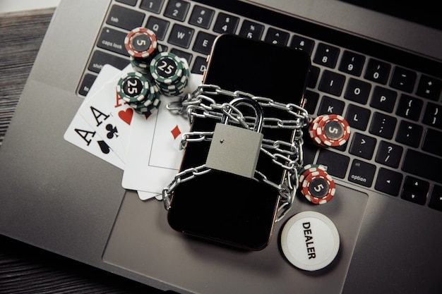 オンラインギャンブルの概念、ラップトップ上の南京錠とトランプを備えたスマートフォンの法律と規則