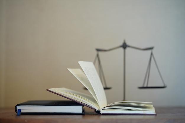 法の本とぼやけた正義のスケールの背景を持つ開いた本