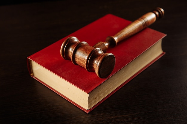 Law book with a judges gavel resting on top of the pages in a courtroom or law enforcement office.