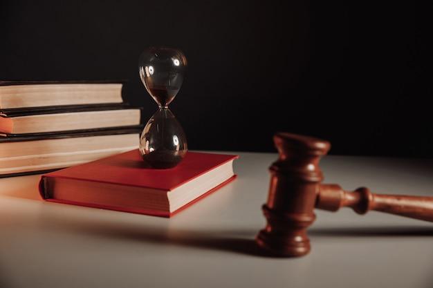 Песочные часы кодекса закона с красной книгой и молотком судьи