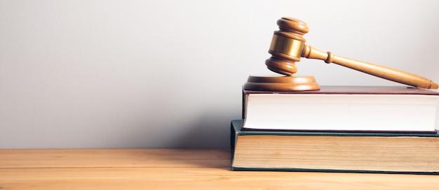 テーブルの上に木製の裁判官のガベルと法の概念の法律の本