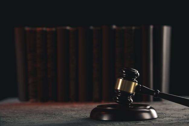 法律の概念-黒い背景の法廷または法執行機関のテーブルに木製の裁判官のガベルで開いた法律の本。