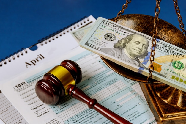 Law concept scales of justice criminal liability for non-payment of taxes of one hundred dollars bill form 1040 on u.s. individual income tax return
