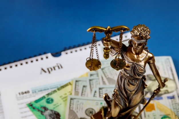 Law concept with statue of justice in many hundred dollars cash money u.s. individual income tax return, form 1040 soft focus
